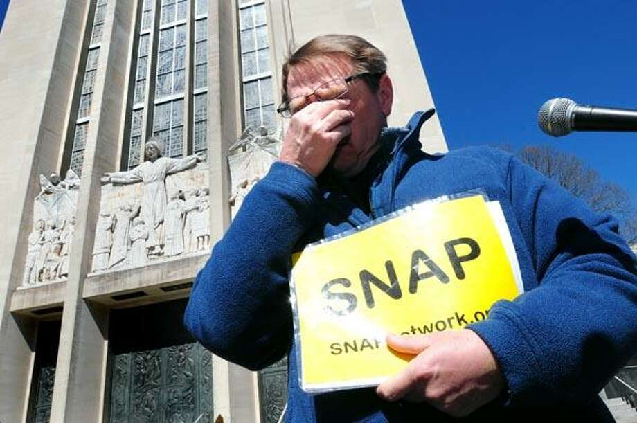 David Clohessy of SNAP (Survivors' Network of those Abused by Priests) covers his eyes during a moment of silence for the child victim's of sexual abuse by clergy who haven't survived before a press conference about alleged sexual abuse victim Jeffrey Libby and his alleged abuser, Rev. Richard McGann, in front of the Cathedral of St. Joseph in Hartford on 3/28/11. Photo by Arnold Gold/New Haven Register