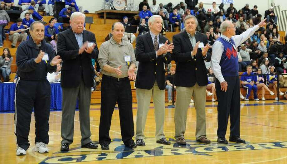 """The University of New Haven's first men's basketball coach and director of athletics, Don Ormrod, points to the retired number of Gary Liberatore during the halftime ceremony honoring the 50th anniversary of UNH athletics. Members of the Chargers' inaugural men's basketball team for the 1961-62 season are, from left, assistant coach Frank """"Porky"""" Vieira, Dick Jackson, Mel Horowitz, Walt Lee, Bob Ruth and Ormrod. (Photo courtesy of University of New Haven Athletics)"""