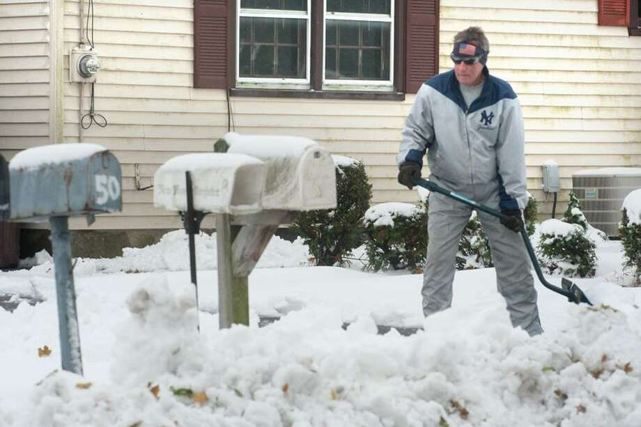 Bernie Guillemette shovels out his driveway Thursday near Shortbeach Road in Branford after last night's nor'easter. VM Williams/New Haven Register