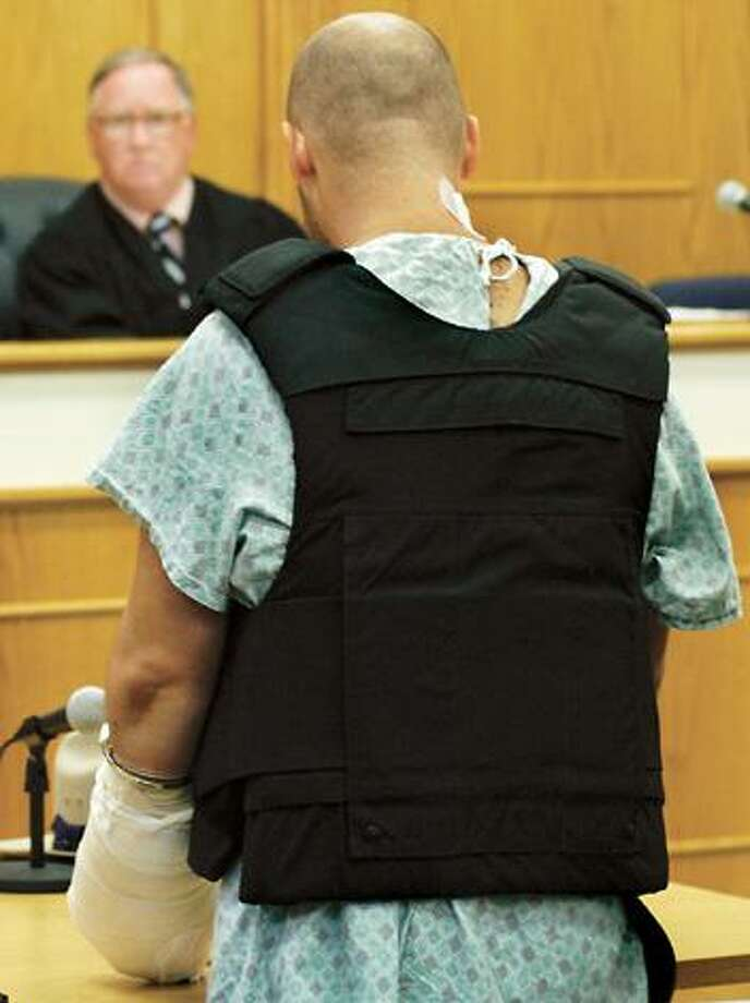 Dispatch Staff Photo by KURT WANFRIEDWearing bandages, a blue hospital gown and a flak jacket David Trebilcock stands before Sherrill City Judge Newal Rose Monday.