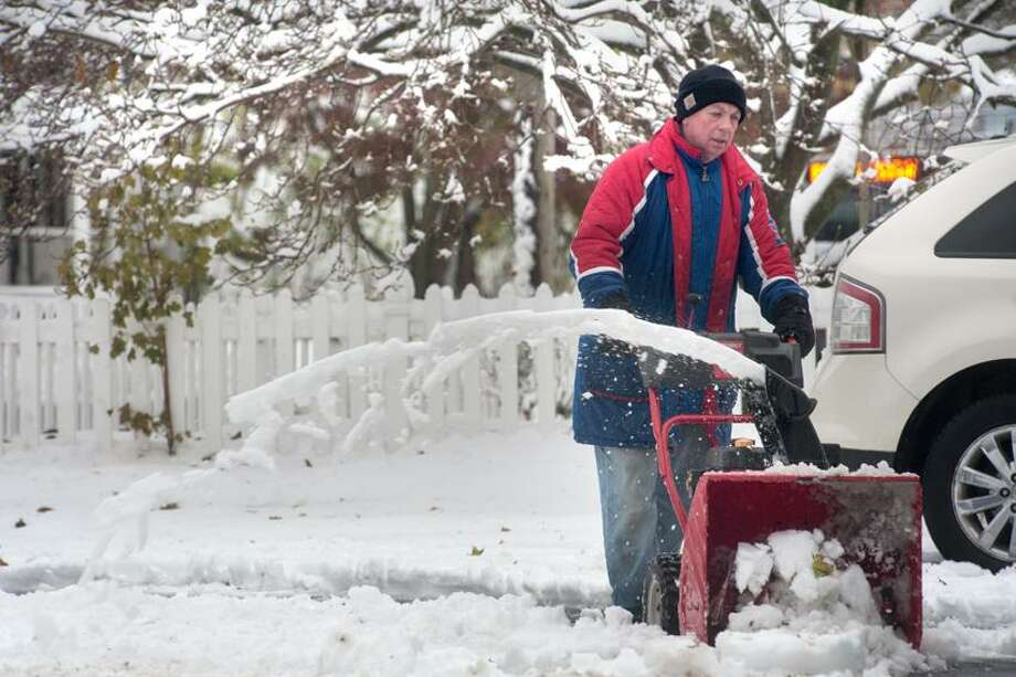 Dave Hainsworth uses a snow blower Thursday to clean the sidewalks at Angel Paws Dog Grooming along Main Street in Branford after last night's nor'easter. VM Williams/New Haven Register