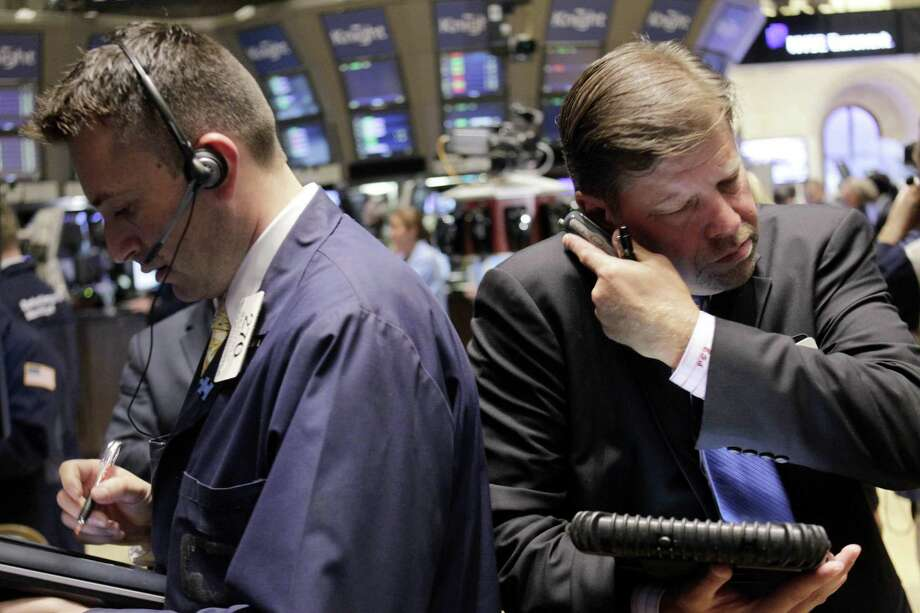 Traders work on the floor at the New York Stock Exchange in New York Monday. (AP Photo/Seth Wenig) Photo: AP / AP