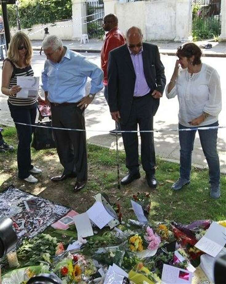 Amy Winehouse's father Mitch, second from left, her mother Janis, right, and other friends look at flowers left by mourners in Camden Square outside the house of Amy Winehouse on Monday.(AP Photo)