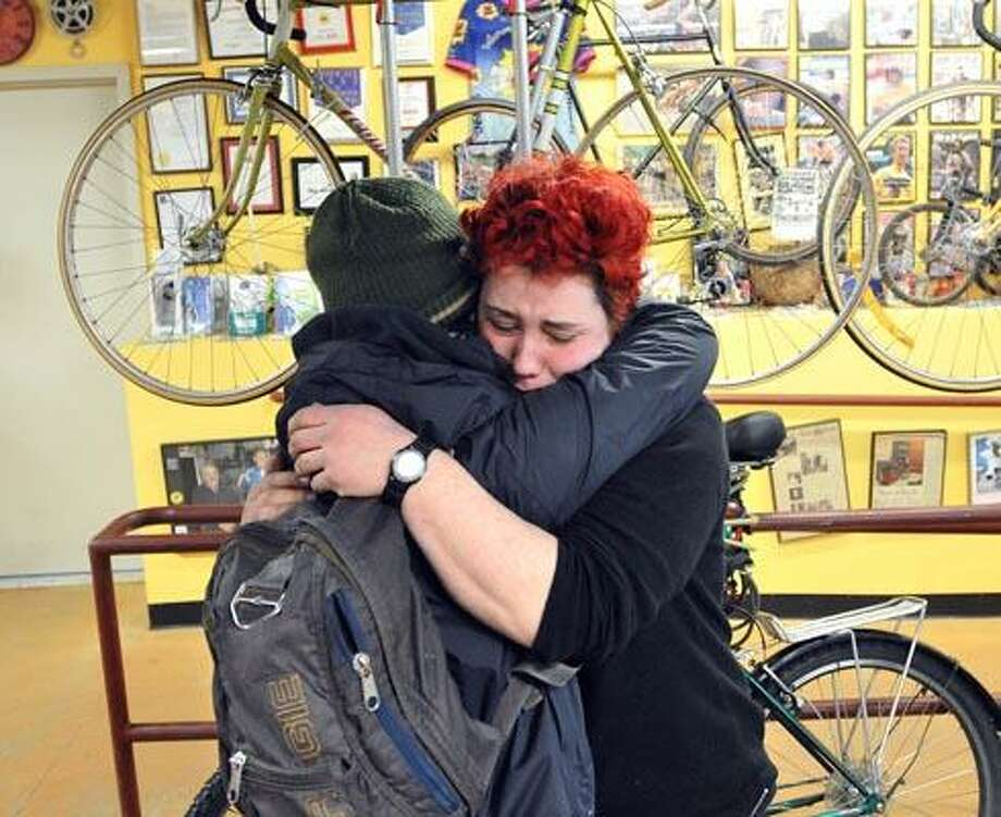 "New Haven--Sara Kirschner (facing camera) hugs customer Hilary Stearns at the Devil's Gear Bike Shop in New Haven as Stearns stopped in to pay her respects to the staff there. Murder victim Mitchell Dubey worked at the shop and was heavily involved in the New Haven cycling and music scene. A teary eyed Stearns said; ""He was a wonderful person..."" Photo by Peter Casolino/New Haven Register03/24/11 Cas110324"