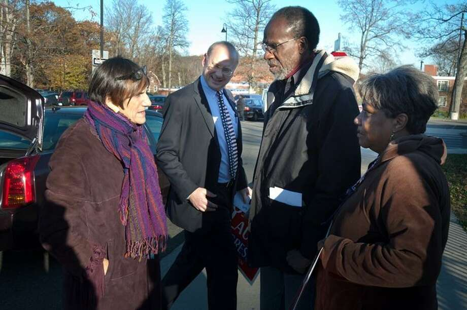 U.S. Rep. Rosa DeLauro speaks to Bill Dyson and Alfreda Edwards as Matthew Nemerson looks on outside Celetano School on Canner Street in New Haven after casting her vote in the election November 6, 2012. vm Williams