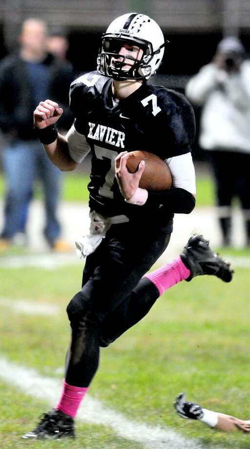 Xavier quarterback Tim Doyle, pictured here scoring a touchdown against Hand last month, hopes to lead the Falcons past West Haven in a clash of top 10 teams Friday night. Photo by Arnold Gold/New Haven Register
