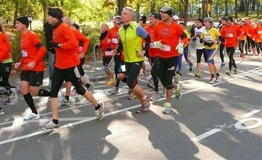 Runners who were planning to run in the New York City Marathon run through Central Park in Manhattan in an alternative marathon in New York, Sunday. AP Photo/Cara Anna Photo: ASSOCIATED PRESS / AP2012