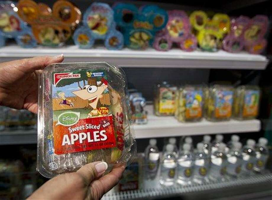 Disney's packed sliced sweet apples is held with other Disney food products, at the Newseum in Washington, Tuesday, June 5, 2012, during a news conference where first lady Michelle Obama and Walt Disney Company announced that Disney will become the first major media company to introduce new standards for food advertising on programming targeting kids and families.    (AP Photo/Manuel Balce Ceneta) Photo: AP / AP
