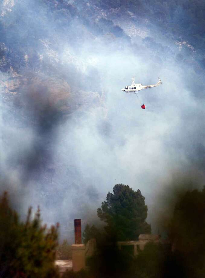 A helicopter flies next over a wildfire in Tuejar, near Valencia, Spain, on Saturday, June 2, 2012. Regional government said wildfire has burned almost 1000 hectares (2400 acres) of forest, while more than 300 firefighters, 8 helicopters and 9 planes are working to stop the fire. (AP Photo/Alberto Saiz) Photo: AP / AP