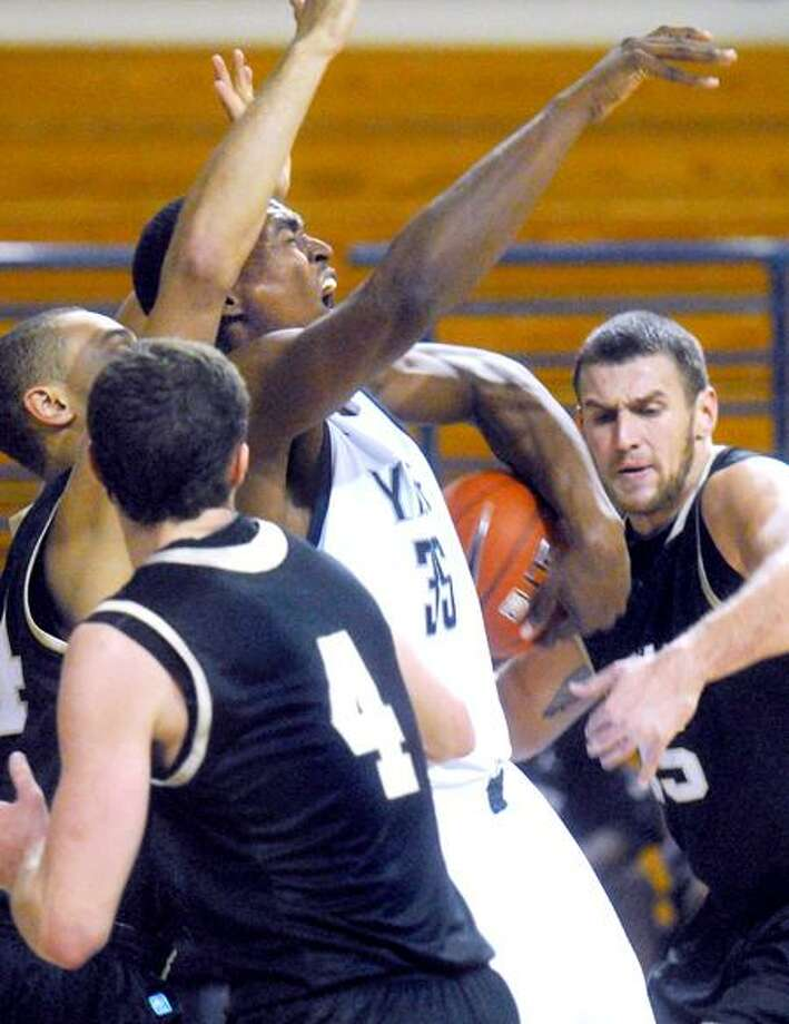 Brandon Sherrod (center) of Yale loses the ball trying to drive through Bryant defenders in the first half on 12/7/2011.Photo by Arnold Gold/New Haven Register    AG0431G