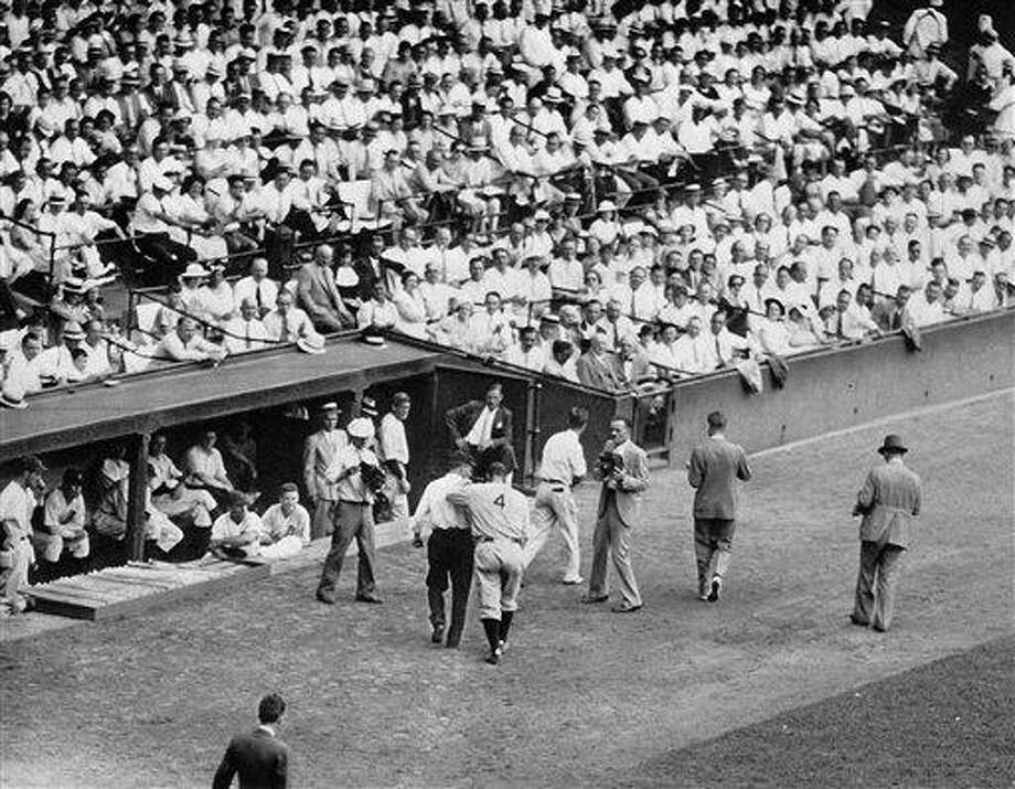 New York Yankees first baseman Lou Gehrig is helped off the field in Detroit on July 13, 1934, with what was described as a lumbago attack, or what would now be more commonly known as back spasms. In the years since, many have speculated that this episode was one of the early symptoms of the disease that eventually felled the Iron Horse. A month earlier, Gehrig missed a game in New Haven to stay in New York and have dental treatment. His consecutive games streak really came to an end in the Elm City, if you count exhibition games. (AP) Photo: AP / 1934 AP