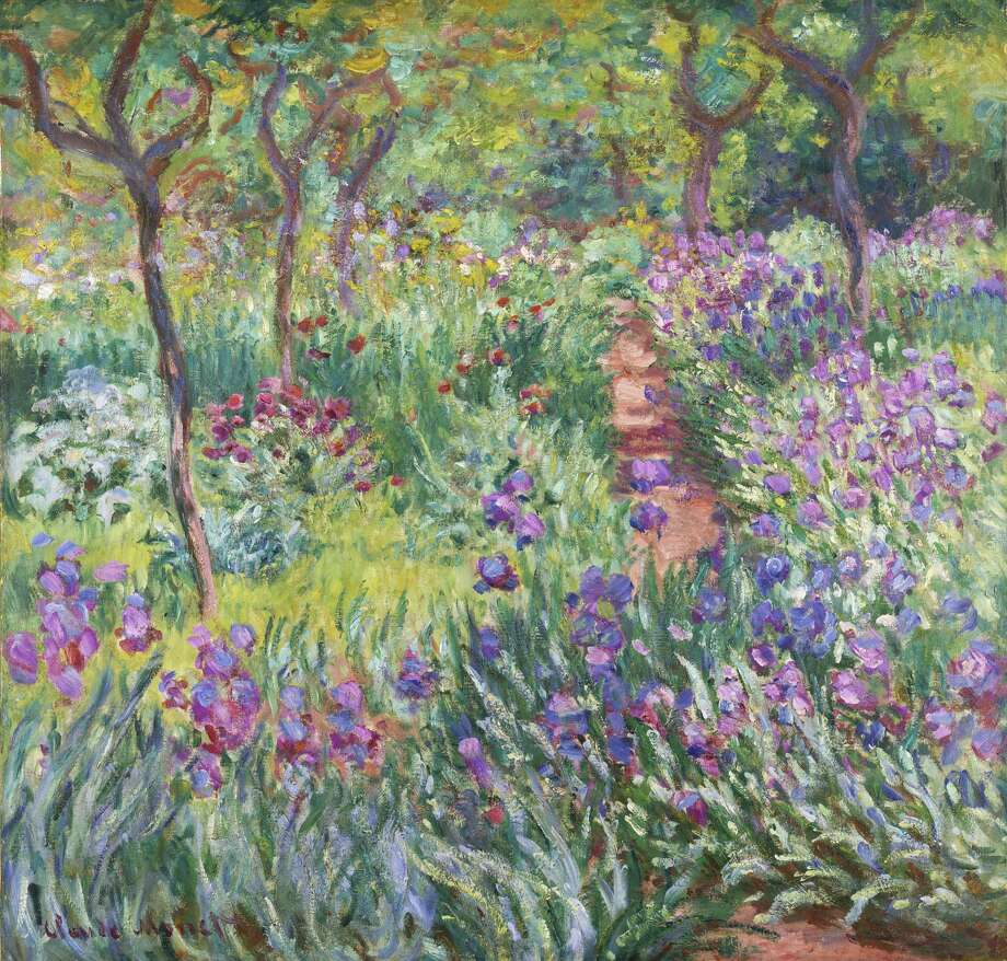 "This undated photo provided by the New York Botanical Garden shows Claude Monet's painting, ""The Artist's Garden in Giverny,"" which is on display in a new exhibition at the New York Botanical Garden, in New York. Monet once said he owed becoming a painter to his love for flowers and the exhibit explores the French impressionist artist's passion for his beloved water lilies, irises and gardens and how they influenced his art. (AP Photo/New York Botanical Garden) Photo: AP / New York Botanical Garden"