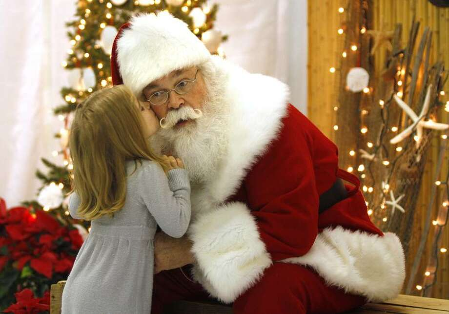 "In this Wednesday, Nov. 30, 2011 photo, Santa, Cliff Snider, gets a kiss on the cheek from Bella Champion, 3, during a Christmas photo shoot at the ""Beach Shack"" in Emerald Isle, N.C. When Snider, who's been playing Santa since he was a teenager, gets a big-ticket request, he typically answers: ""There's an awful lot of children asking for that this year. What else do you want?""     (AP Photo/Tom Copeland) Photo: AP / FR170645 AP"