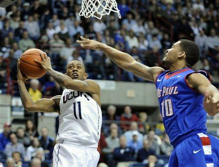 Connecticut's Ryan Boatright (11) drives past DePaul's Derrell Robertson during the second half of  an NCAA college basketball game in Storrs, Conn., on Wednesday, Feb. 15, 2012. Connecticut won 80-54. (AP Photo/Fred Beckham) Photo: AP / FR153656 AP