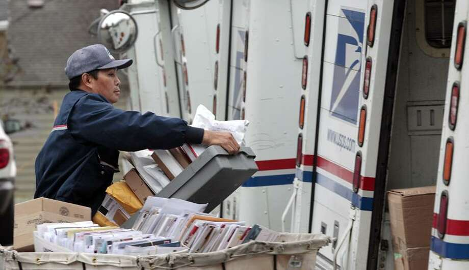 Letter carrier Diosdado Gabnat moves boxes of mail into his truck for delivery Monday at a post office in Seattle. Photo: AP / AP