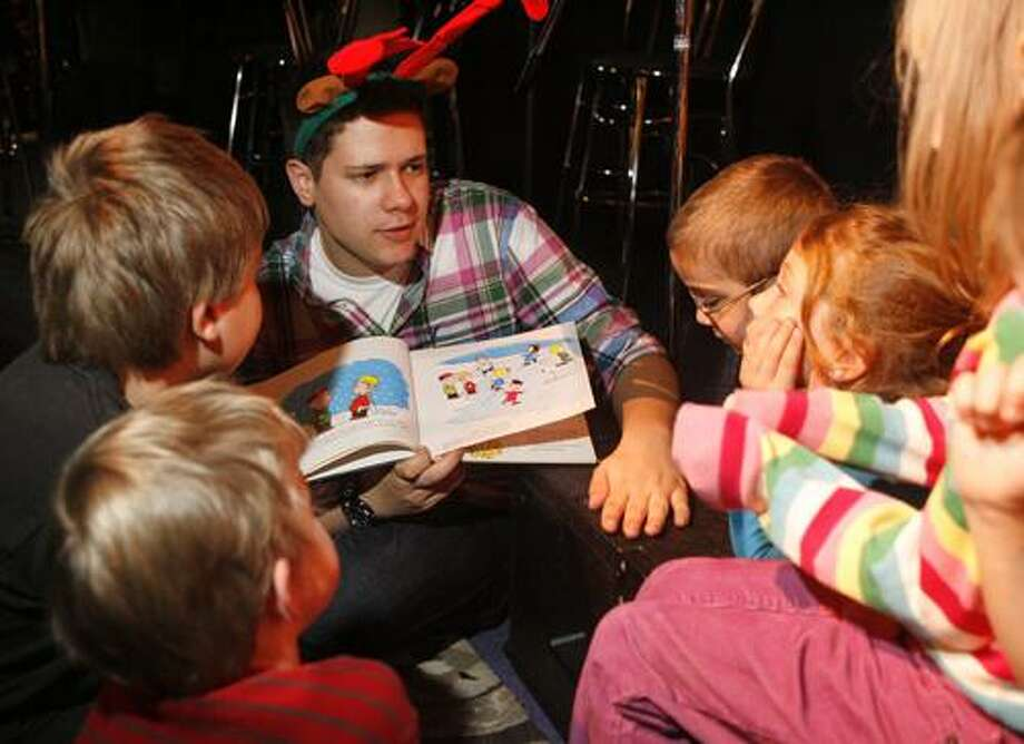 """Dispatch Staff Photo by JOHN HAEGER <a href=""""http://twitter.com/oneidaphoto"""">twitter.com/oneidaphoto</a> Ben Gorton of  Hamilton  reads a holiday book to children during the annual Here Comes Santa at the Palace Theater  in Hamilton  on Saturday, Dec. 3, 2011."""