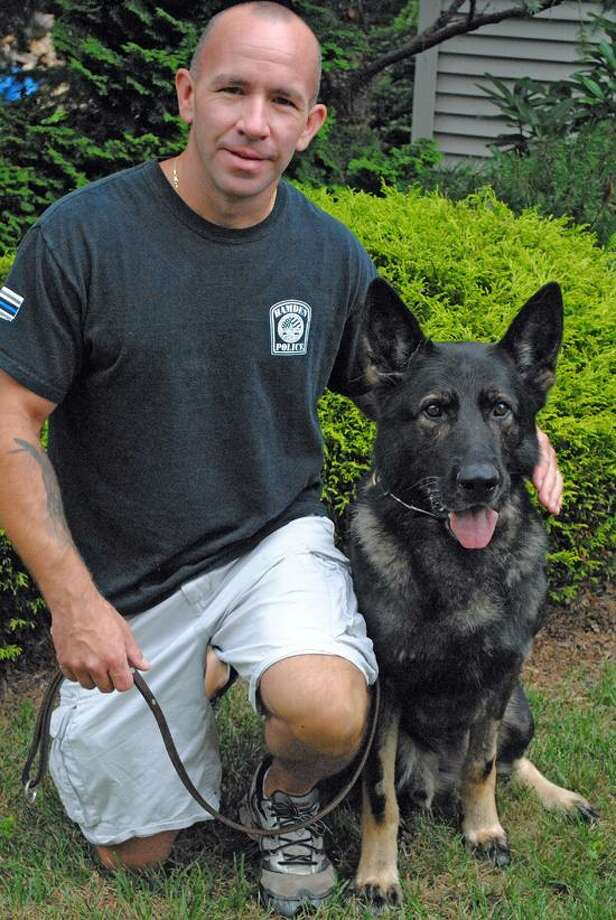 Officer Jay Venditto from Hamden police poses with his K-9 Titan who has been a Hamden police dog for years and recently underwent surgery for two ruptured discs. Photo by Jen Fengler/for the Register