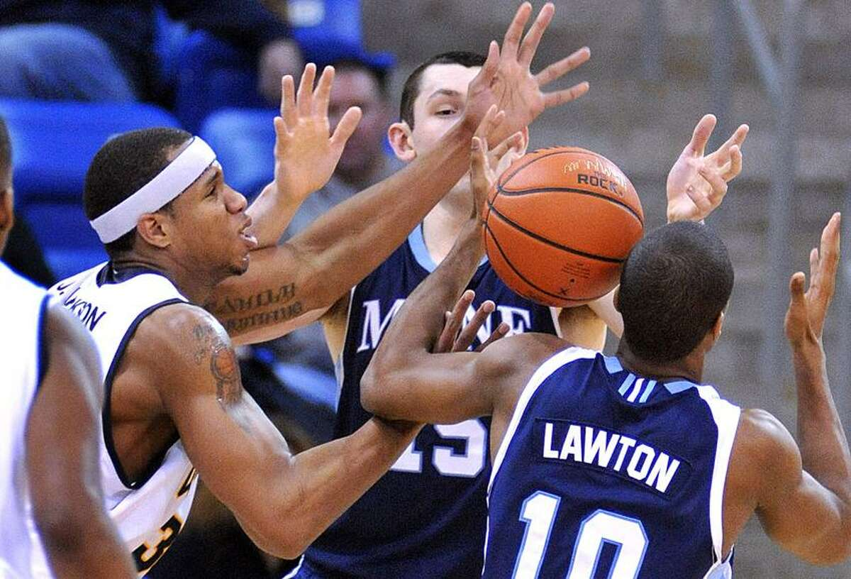 Hamden-- Quinnipiac's Jamee Jackson battles for a rebound against Maine's Alasdair Fraser, left, and Shaun Lawton during the second period . Photo-Peter Casolino 12/29/12,