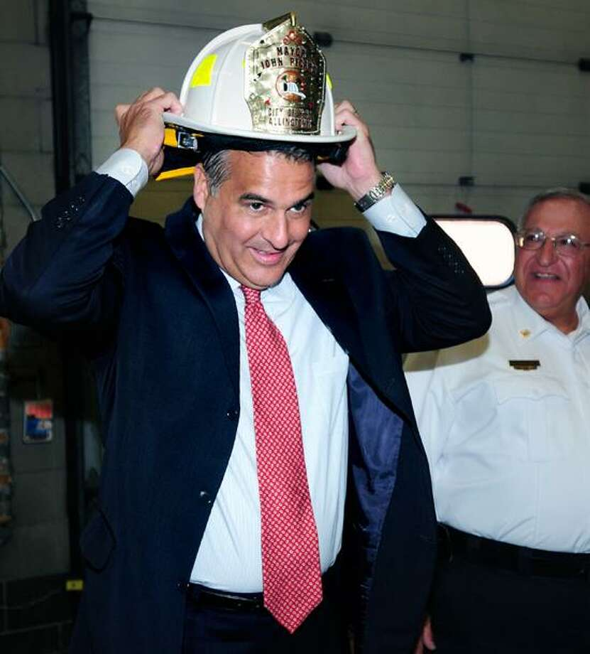 West Haven Mayor John Picard puts on an honorary fire helmet presented to him by Allingtown Chief Peter Massaro, right, at the Minor Park fire station to symbolize the merger of the Allingtown Fire District with the city of West Haven. Photo by Arnold Gold/New Haven Register