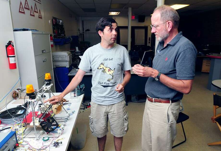 JR Logan, left, of New Haven talks about the home built 3D printer to Bill Neale, right, president of the New Haven Manufacturers Association, at Make Haven on State Street in New Haven. Photo by Arnold Gold/New Haven Register