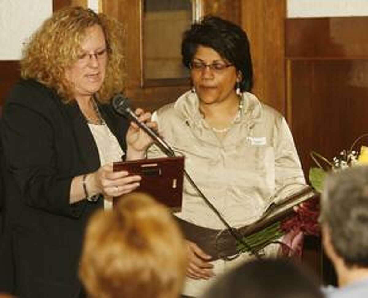 Dispatch Staff Photo by JOHN HAEGER Zonta member Amy Jennings reads a plaque as she presents it to Rathika Martyn, MD on Wednesday, March 16, 2011. Martyn is the recipeient of the Zonta's 2011 Status of Women Award.