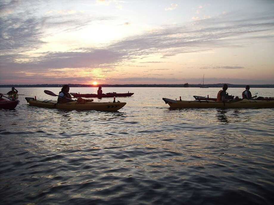 Martin Torresquintero photo: Paddlers will be out on the water after sunset Thursday night at Lighthouse Point Park in New Haven.