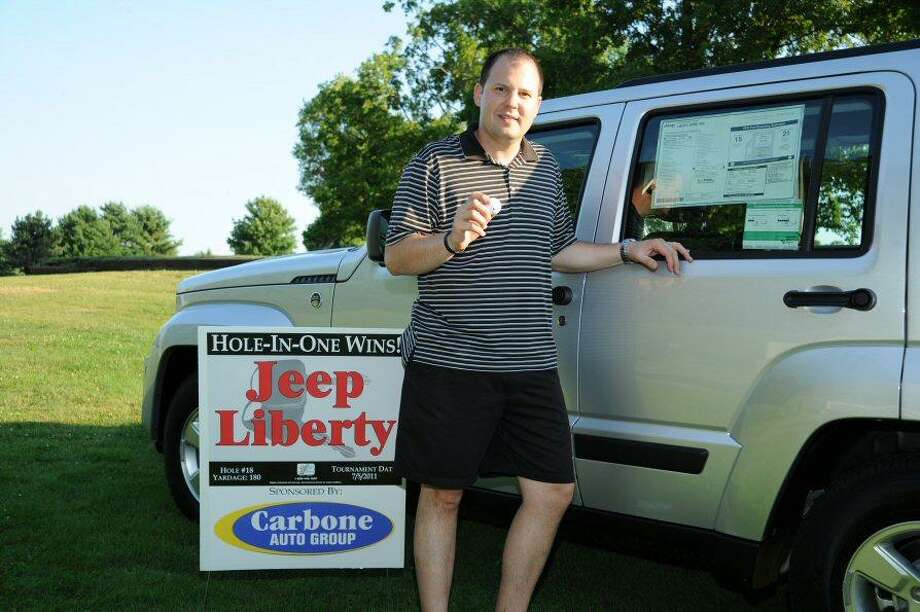 Submitted Photo Dave Faccioli of Utica shows off the car he won after a hole-in-one at the Boilermaker golf tournament.