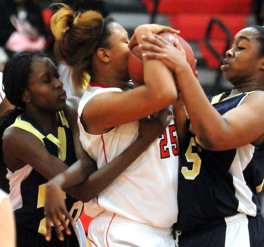 Hyde's Dominique Burgess, left, and Tahnajia Daniels right surround Wilbur Cross' Heaven Daluz on a rebound under the Cross basket during Hyde's win on Wednesday. Mara Lavitt/New Haven Register