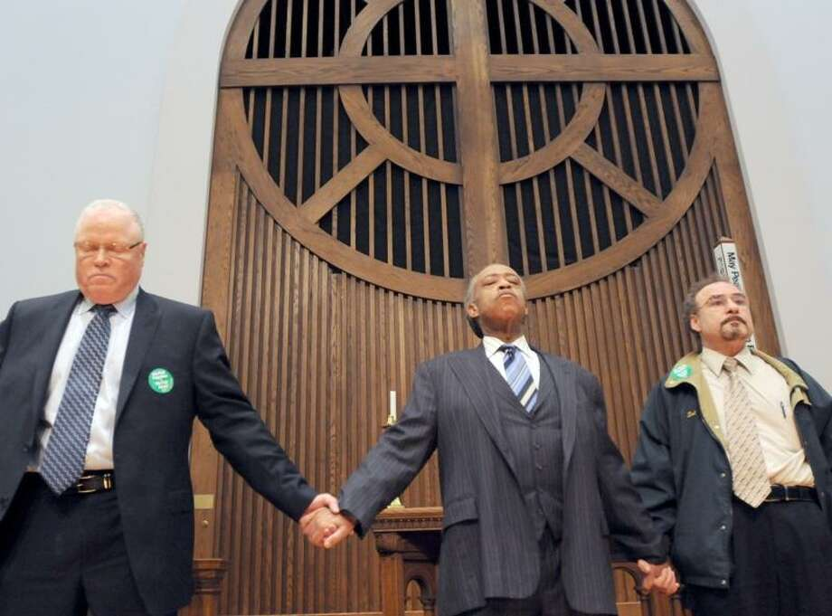 Rev. Al Sharpton of the National Action Network, center, flanked by Lee Saunders, Secretary-Treasurer of the AFSCME AFL-CIO, left, and Sal Luciano, Executive Director of Council 4 AFSCME, right, holds hands as they pray after a rally in support of City of New Haven workers and against anti-union sentiments of municipal and state government officials nationwide during a union rally Monday 3/14/11at the United Methodist Church in New Haven supporting City of New Haven unions. Photo by Peter Hvizdak / New Haven Register