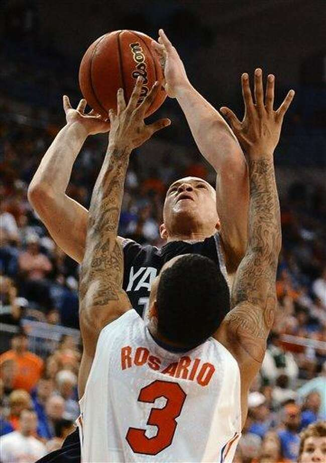 Florida's  Mike Rosario (3) blocks a shot by Yale's Austin Morgan (1) during the second half of an NCAA college basketball game in Gainesville, Fla., Saturday, Dec. 31, 2011. Florida defeated Yale 90-70. (AP Photo/Phil Sandlin) Photo: ASSOCIATED PRESS / AP2011