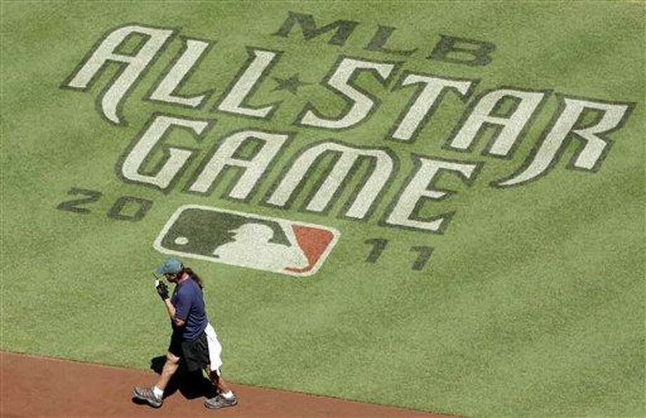 A member of the television broadcast crew walks past a painted All-Star game logo as they get Chase Field ready for the MLB All-Star baseball game Saturday, July 9, 2011, in Phoenix.  The game will be held on Tuesday, July 12. (AP Photo/Ross D. Franklin) Photo: AP / AP