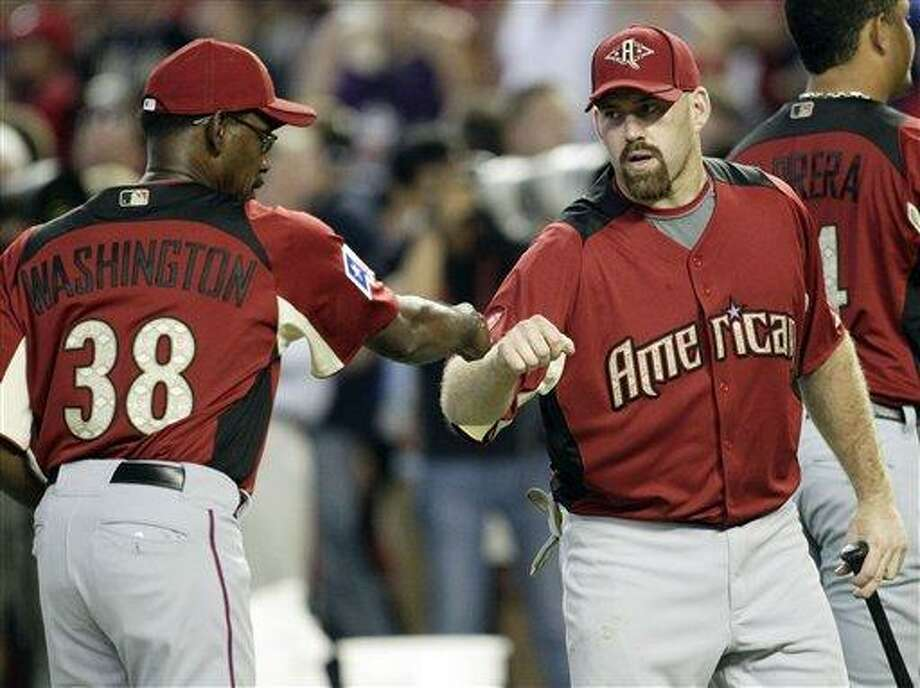 American League manager Ron Washington of the Texas Rangers fist pumps with American League's Kevin Youkilis of the Boston Red Sox during batting practice for the MLB All-Star baseball game Monday, July 11, 2011, in Phoenix. (AP Photo/Matt York) Photo: AP / AP