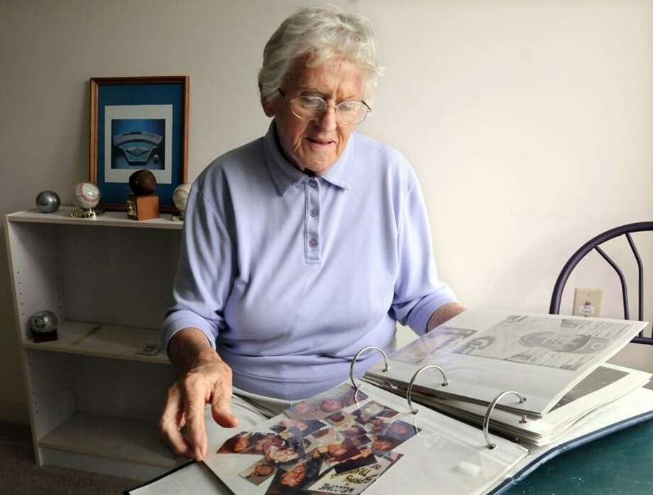 Jean Kaas looks through a scrapbook of the baseball minor league players who she hosted while living in West Haven. Photo by Mara Lavitt/New Haven Register
