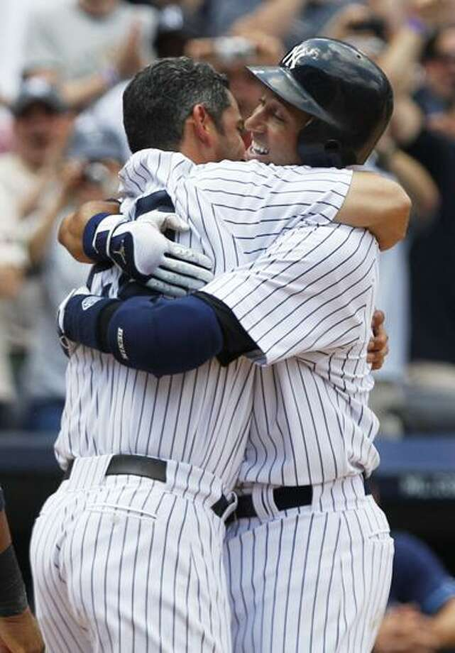 New York Yankees' Derek Jeter, right, hugs teammate Jorge Posada after hitting a home run for his 3,000th career hit during the third inning of a baseball game against the Tampa Bay Rays, Saturday, July 9, 2011, at Yankee Stadium in New York. Jeter became the 28th major leaguer to hit the milestone and also the first Yankees player. (AP Photo/Frank Franklin II) Photo: AP / AP