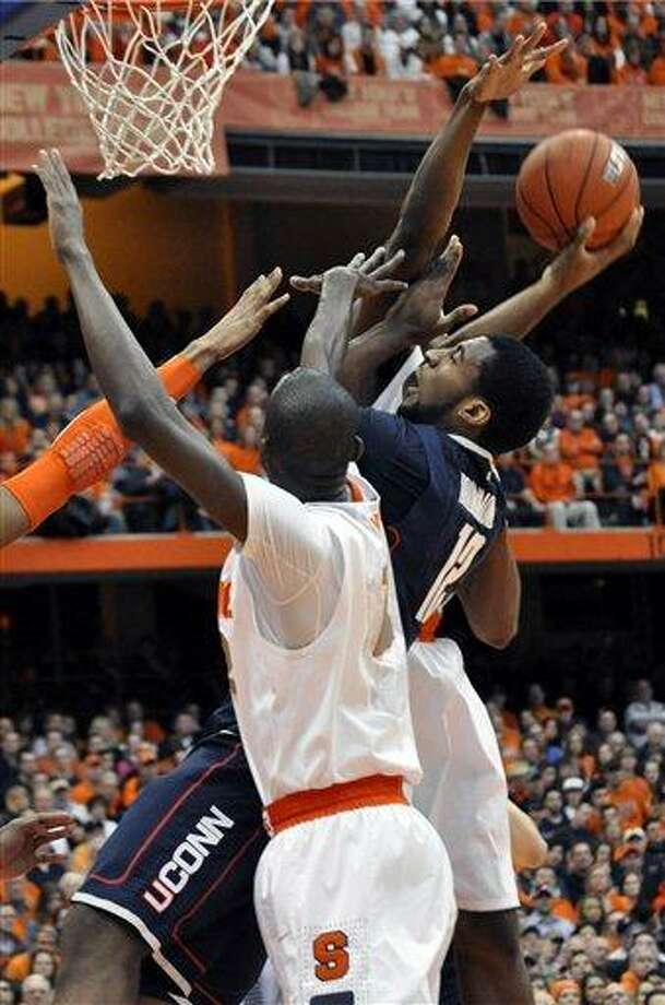 Connecticut's Andre Drummond tries to score between Syracuse defenders during the first half of an NCAA college basketball game in Syracuse, N.Y., Saturday, Feb. 11, 2012. (AP Photo/KevinRivoli) Photo: AP / FR60349 AP