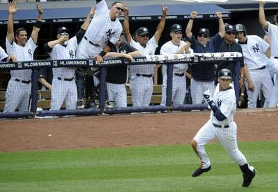 New York Yankees' Derek Jeter, bottom right, watches his home run for his 3,000 career hit as his teammates react during the third inning of a baseball game against the Tampa Bay Rays Saturday, July 9, 2011 at Yankee Stadium in New York. (AP Photo/Bill Kostroun) Photo: AP / FR51951 AP