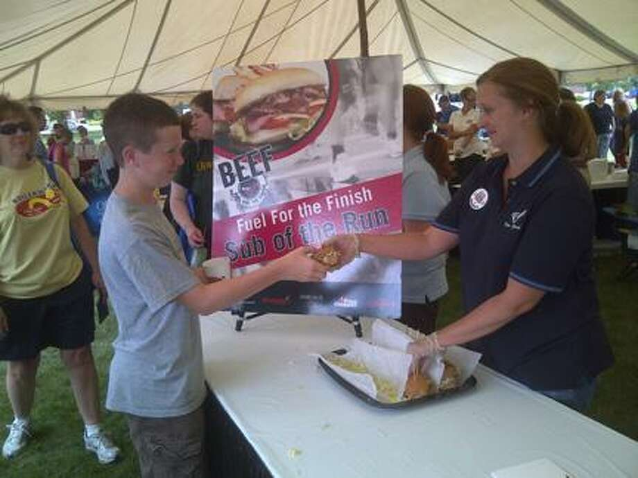Submitted Photo A Boilermaker Expo fan gets part of a roast beef sub for free at the New York Beef Industry Council's exhibit Friday at the Masonic Home in Utica. The annual 15k road race starts at 8 a.m. on Sunday. The expo continues today.