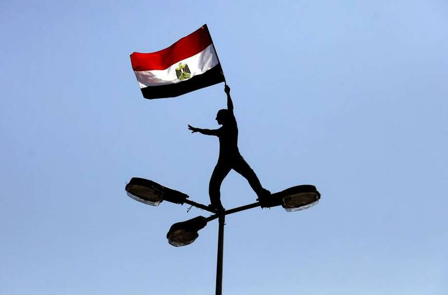 A protester waves the Egyptian flag as he stands on top of a street lamp in Cairo Friday. Associated Press Photo: AP / AP