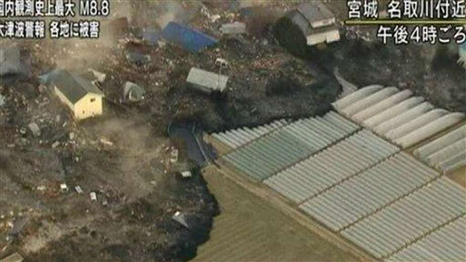 In this video image taken from Japan's NHK TV, a tsunami surge carrying debris sweeps between houses to reach poly tunnels on farmland near Sendai in Miyagi Prefecture Japan Friday March 11, 2011 following a massive earth quake. A magnitude 8.9 earthquake slammed Japan's northeastern coast Friday, unleashing a 13-foot (4-meter) tsunami that swept boats, cars, buildings and tons of debris miles inland. Fires triggered by the quake burned out of control up and down the coast. (AP PHOTO/NHK TV) Photo: AP / NHK TV