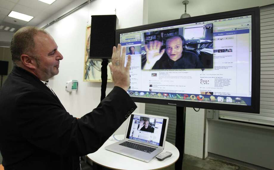 Facebook workers Mike Barnes, left, Video Chats with Jonathan Rosenberg, right, on Facebook during an announcement at Facebook headquarters in Palo Alto, Calif., Wednesday. (AP Photo/Paul Sakuma) Photo: AP / AP