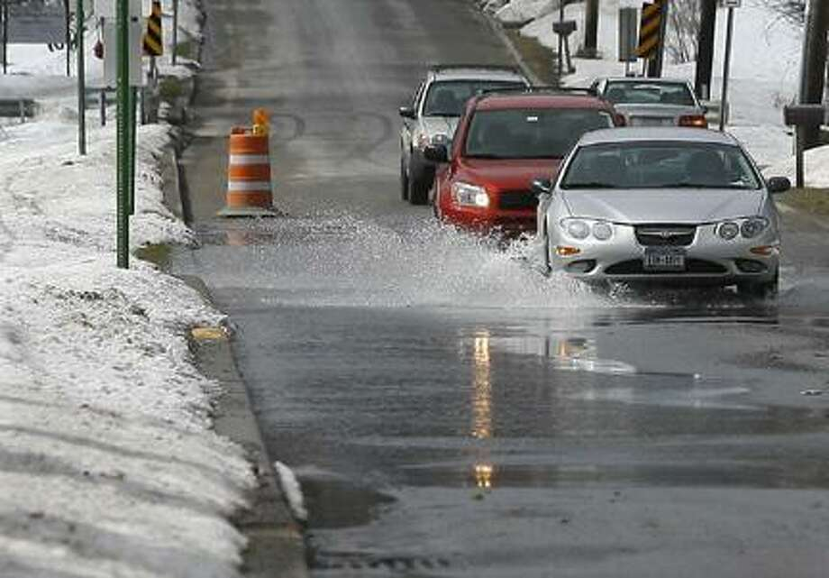 Dispatch Staff Photo by JOHN HAEGERVehicles travel down College Street in Hamilton as water floods a section of the road on Friday, March 11, 2011.
