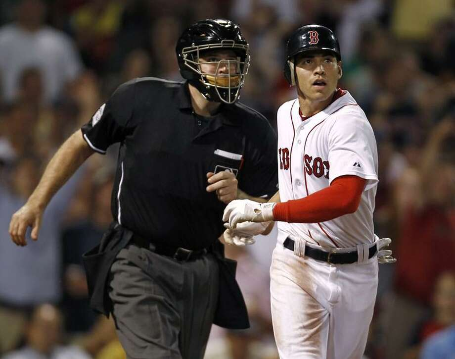 Boston Red Sox's Jacoby Ellsbury is bumped by home plate umpire Bill Welke as they look to see if a ball hit by Ellsbury was fair, during the sixth inning of a baseball game against the Baltimore Orioles at Fenway Park in Boston on Thursday, July 7, 2011. The ball stayed fair for a home run. (AP Photo/Winslow Townson) Photo: AP / FR170221 AP