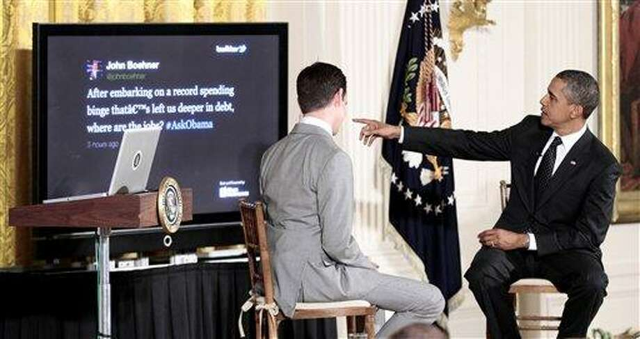 President Barack Obama, accompanied by Twitter co-founder and Executive Chairman Jack Dorsey, left, points to a question on the screen posted by House Speaker of the House John Boehner of Ohio, during the first ever Twitter Town Hall, Wednesday, July 6, 2011, in the East Room of the White House in Washington. (AP Photo/Pablo Martinez Monsivais) Photo: AP / AP