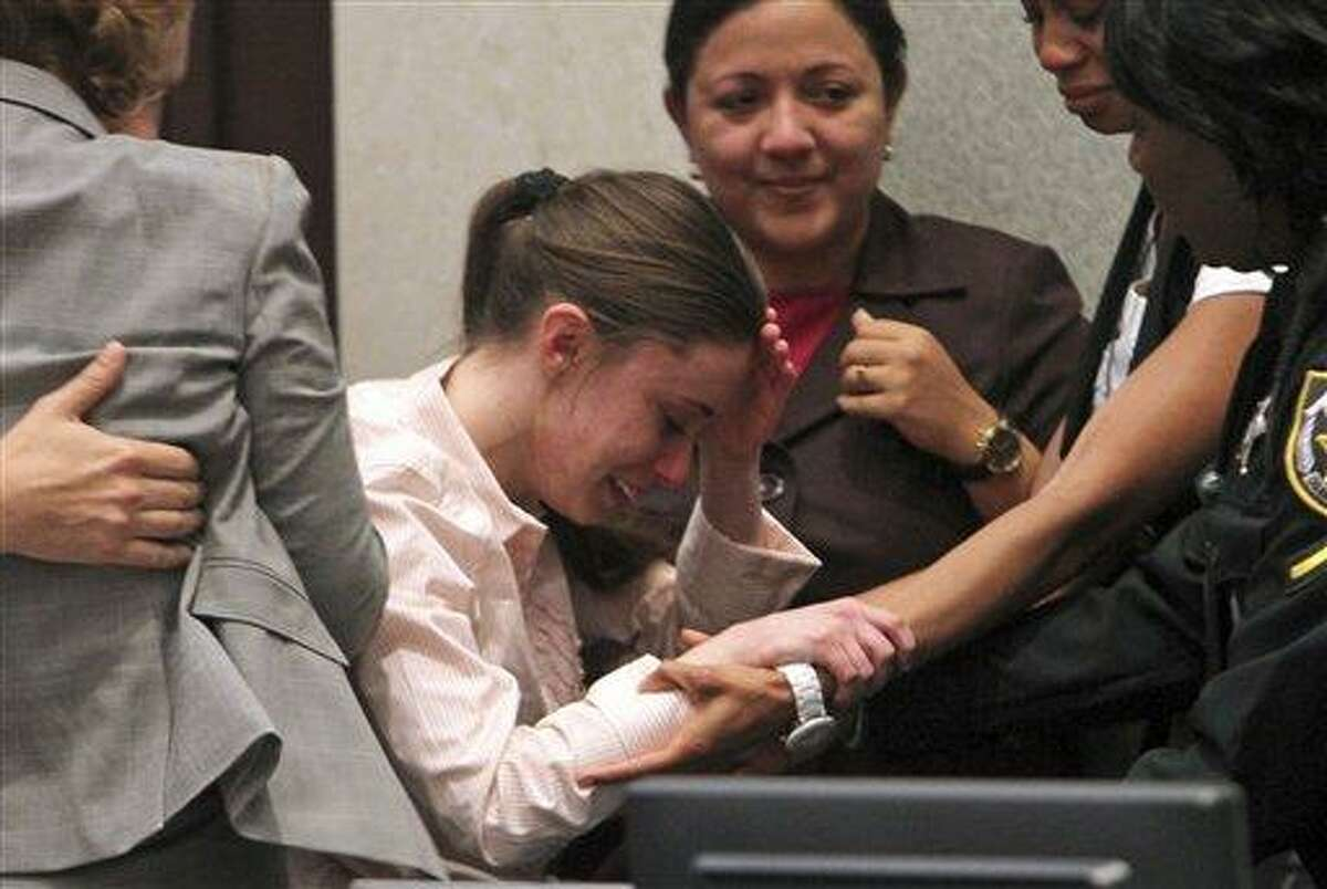 Casey Anthony, center, is overcome with emotion following her acquittal of murder charges at the Orange County Courthouse in Orlando, Fla., Tuesday, July 5, 2011. Anthony had been charged with killing her daughter, Caylee. (AP Photo/Red Huber, Pool)