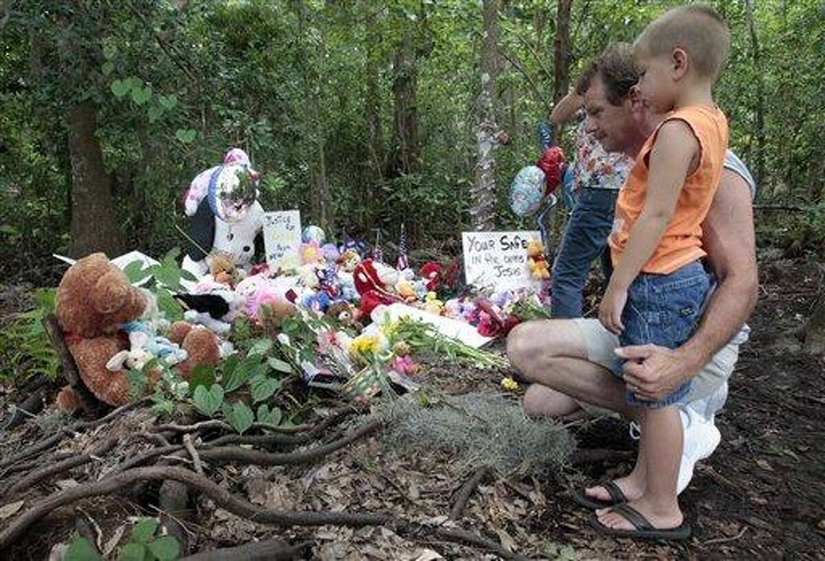 Alan Holt and his grandson Mark Likins, of Thomasville, Ga., visit the memorial of Caylee Anthony before Casey Anthony was found not guilty of first-degree murder, aggravated manslaughter and aggravated child abuse. in Orlando, Fla., Tuesday, July 5, 2011. (AP Photo/Alan Diaz)
