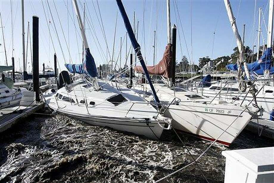 Sailboats in the Santa Cruz Harbor crash against each other Friday , March 11, 2011 in Santa Cruz, Calif. A tsunami triggered by the massive earthquake in Japan rushed onto California's coast Friday, causing powerful surges that destroyed boat docks as beach-area residents throughout the state evacuated to higher ground. (AP Photo/Santa Cruz Sentinel, Dan Coyro) Photo: AP / AP