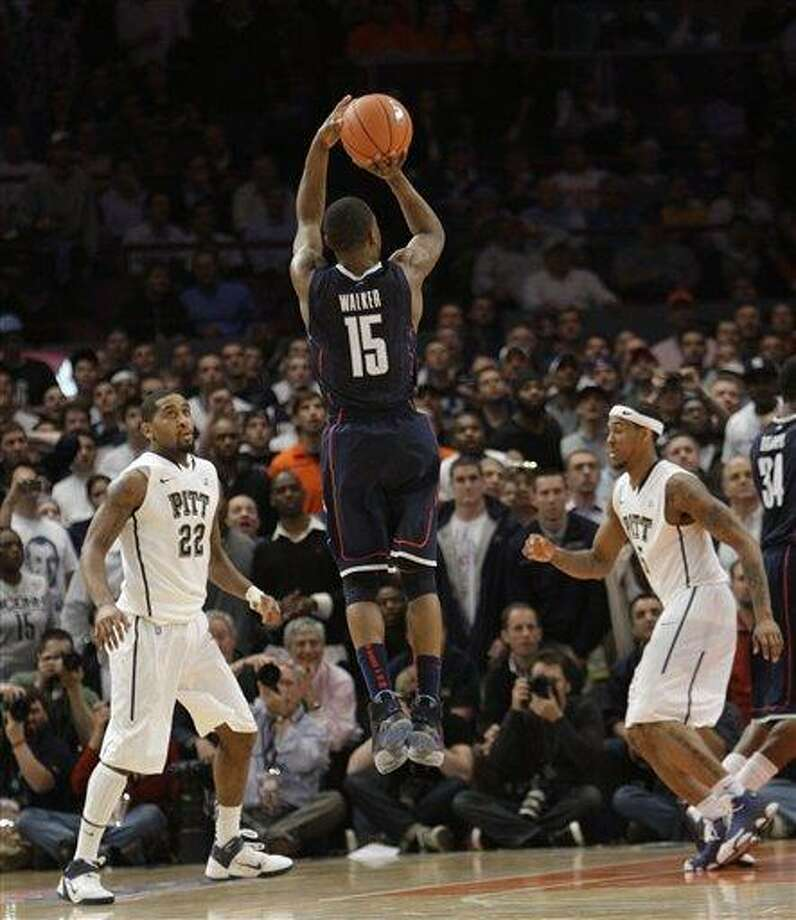 Connecticut's Kemba Walker goes up for what will be the winning  basket during the final seconds of the second half of an NCAA college basketball game at Brad Wanamaker and Gilbert Brown watch at the Big East Championship, Thursday, March 10, 2011 at Madison Square Garden in New York.  Connecticut defeated Pittsburgh 76-74. (AP Photo/Mary Altaffer) Photo: AP / AP