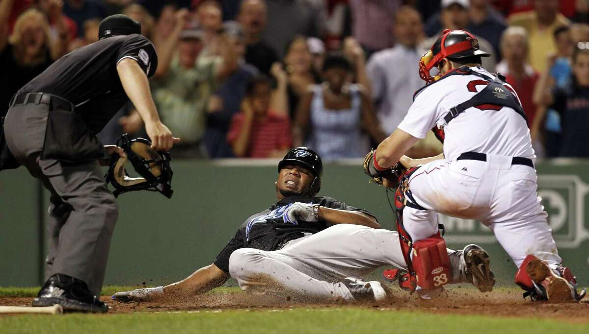 Toronto's Edwin Encarnacion slides into home plate and is tagged out by Boston's Jason Varitek for the final out of Tuesday's 3-2 Red Sox win. (AP photo)