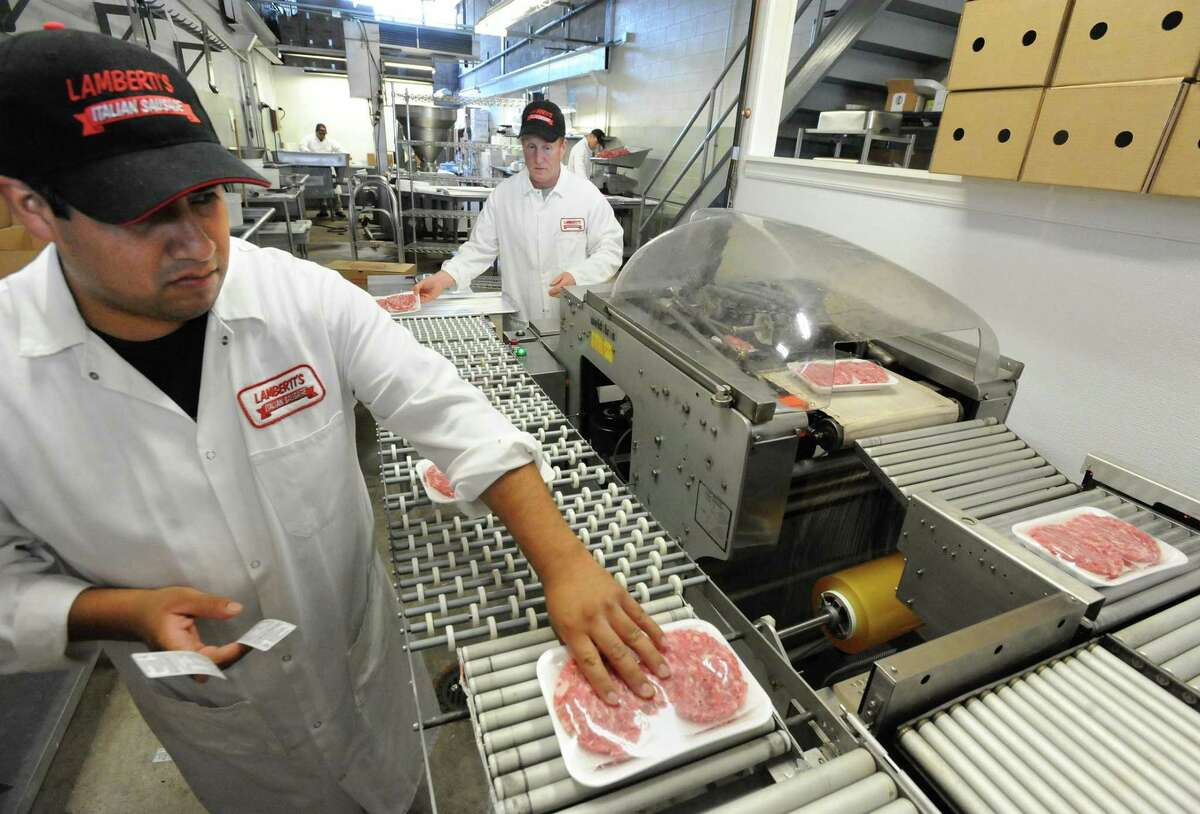 Aaron Badilla, left, and Joseph Kelley package sausage patties at Lamberti Sausage Company, which is celebrating its 65th year in business. (Photo by Brad Horrigan/New Haven Register)