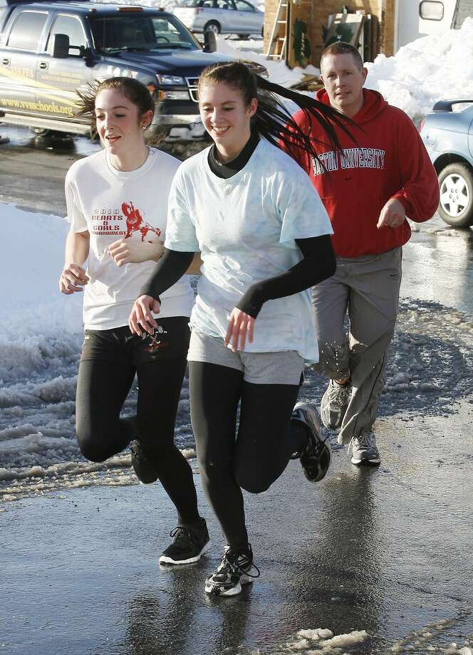 Dispatch Staff Photo by JOHN HAEGER VVS track team members Alexis Kavanaugh, left, and Alyssa Durant, middle, train as coach Todd Bauer follows behind Tuesday, March 8, 2011 at the high school.